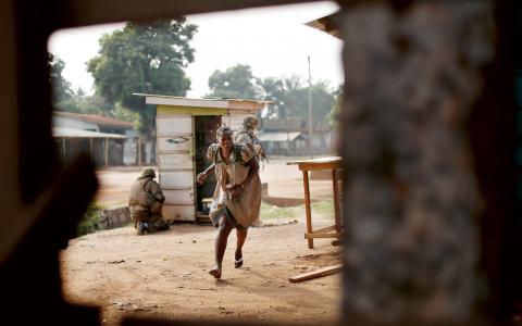 En kvinna försöker ta sig skydd när tung skottlossning bryter ut i centrala Bangui.  Bild: Jerome Delay/AP