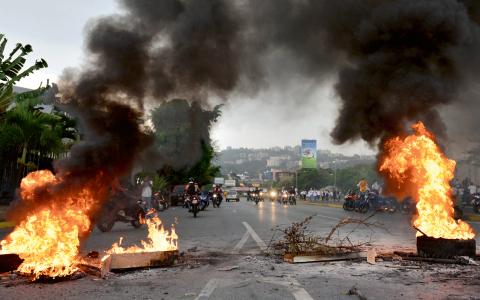 Anhängare till Leopoldo López har satt eld på däck för att blockera en huvudgata i Caracas, i protest mot att deras ledare överlämnade sig till myndigheterna i tisdags.  Bild: Carlos Becerra/AP/TT