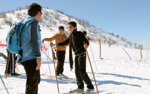 Igor Urizar från Spanien lär syriska flyktingbarn att åka längdskidor.  Bild: Nuzha Ezzat/IPS