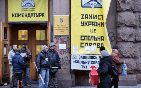 Ingången till det ockuperade jordbruksdepartementet i centrala Kiev. Utanför står beväpnade milismän från den ultranationalistiska rörelsen Spilna Sprava.  Bild: Linus Waltersson