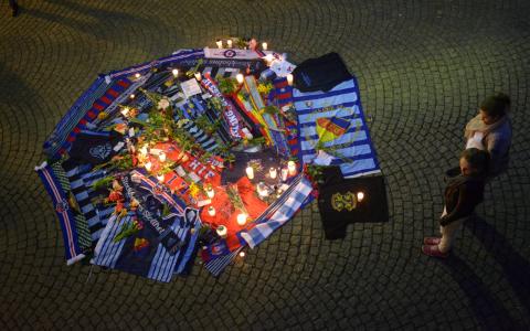 Ljus, blommor, tröjor och halsdukar på den plats vid Kärnan i Helsingborg där en supporter skadades så svårt att han avled innan söndagens allsvenska match mellan Helsingborgs IF och Djurgårdens IF. Bild: Johan Nilsson/TT