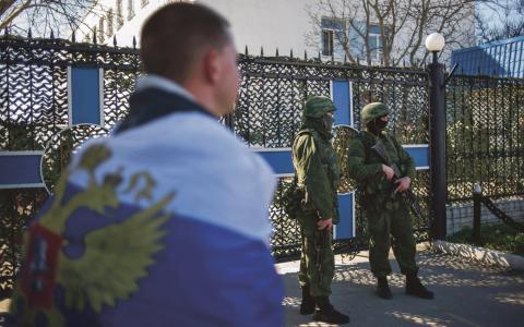 En prorysk anhängare draperad i den ryska flaggan går förbi en militärbas i Sevastopol på Krimhalvön i Ukraina.  Bild: Andrew Lubimov/AP