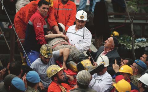Räddningsarbetare för bort en skadad gruvarbetare ur rasmassorna. Gruvolyckan i Soma är Turkiets hittills värsta och fick landets fackförbund att utlysa strejk i protest mot den bristande säkerheten.  Bild: Emrah Gurel/AP/TT