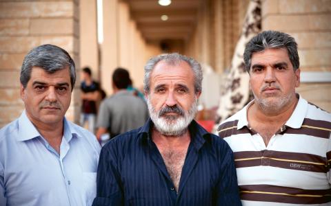 Saad Noori från Stockholm, till vänster, tillsammans med sin morbror och bror i flyktinglägret utanför Sankt Josefskyrkan.  Bild: Thorkil Rothe