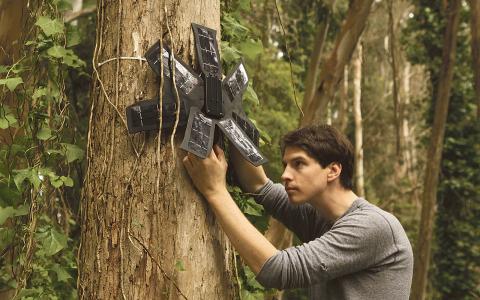 Topher White visar hur solcellerna och mobiltelefonen fungerar ihop. De monteras sedan högt upp i träden, där de inte syns från marken. Bild: Rainforest Connection