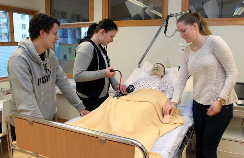 Viktor Nordström, Amanda Björk och Clara Jönsson mäter blodtryck och puls på ED:s nyinköpta simulatordocka BILD: THOMAS JOKINIEMI