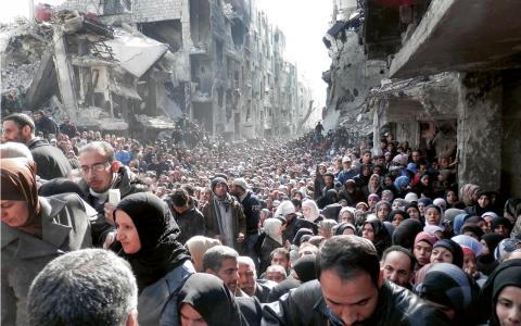 Människor som köar för förnödenheter i flyktinglägret Yarmouk nära Damaskus i januari 2014. När bilden publicerades fick den enorm spridning och ledde till att många fick upp ögonen för hur Syrienkriget slagit hårt mot civilbefolkningen. Bild: AP