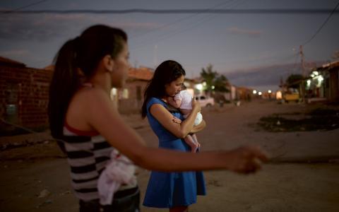 Milena Kaline, 17, är gravid i tredje månaden och håller Angelica Pereiras dotter Luiza i famnen, som föddes med mikrocefali för tre månader sedan. De bor i Santa Cruz do Capibaribe i Brasilien, som drabbats hårt av zikaviruset. Bild: Felipe Dana/TT