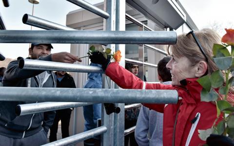 En kvinna delar ut blommor till en man på ett flyktingboende i Köln. Bild: Martin Meissner/AP