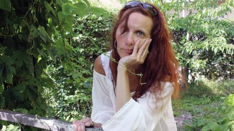 """Författaren Stina Nilsson Bassel utanför sitt hus i Röda stan. """"Jag älskar att skriva. Allting har en berättelse. Och man hoppas att det man skriver kan stöka till lite i någon i alla fall, om än inte i varje läsare"""", säger hon.  Bild: Press"""