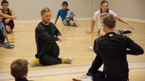 Tobias Marin, som organiserar Breaking-SM i Norrköping, visar sina elever hur man stretchar ordentligt innan man dansar.  Bild: Lucas de Vivo