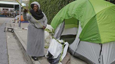 Den hemlösa kvinnan Angela Flax packar ihop sitt tält vid Division street i San Francisco. Bild: Eric Risberg/AP