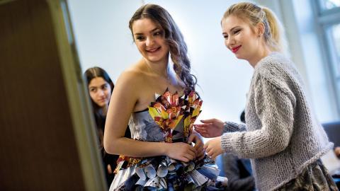 Sibela Demiri och Louise Ekblom provar klänningen på Mirna Alnahi som inledningsvis tecknade klänningen. Nu får hon känna hur modellen känns att bära, och den är tung, eftersom minst 30 tidningar har gått åt till skapelsen. Bild: Kicki Nilsson/Icon Photography
