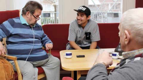Aref Hazareh trivs med de äldre på träffpunkten Granen på Sankt Persgatan. Här tillsammans med Bo Ringqvist och Sven Ferdinandsson.  Bild: Lisa Karlsson