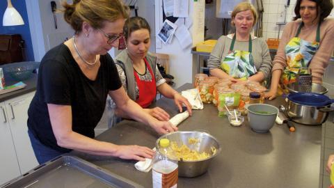 Kursledaren Ramona och gästen Gittan rullar äppelpaj tillsammans i köket. Mirjam och Sara överblickar det hela. Bild: Gustav Gelin