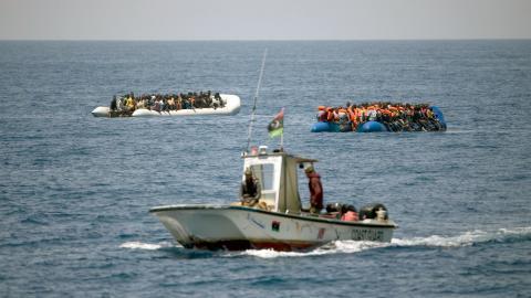 En kustbevakningsbåt från Libyen och två överfulla gummibåtar med flyktingar      och migranter 3o kilometer utanför Libyens kust.  Bild: Emilio Morenatti/AP/TT