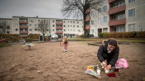 Suzan, 50, som bor i området tänder ljus för att hedra ett av offren efter en skottlossning på en innergård i stadsdelen Tynnered i Göteborg under förra året.  Bild: Björn Larsson Rosvall/TT