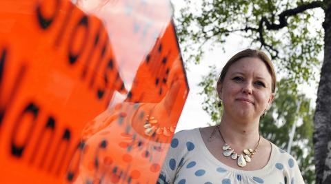 """Caroline Närhi vid en av få gator i Västerås som har uppkallats efter kvinnliga profiler, Nanna Svartz (läkare och professor i medicin vid Karolinska institutet). """"Det är så himla viktigt att lyfta fram de kvinnor som har gjort viktiga insatser"""". Bild: Joni Nykänen"""