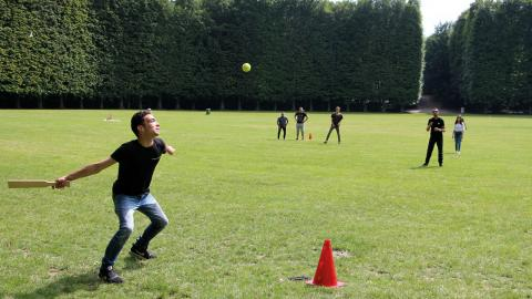 Nittonåriga Kamel Ammauasa slår iväg bollen på brännbollsplanen i den turnering som han själv har varit med och arrangerat. Bild: Jenny Wickberg