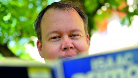 "Håkan Wester bläddrar i Isaac Asimovs hyllade science fiction-roman ""Stiftelsen"".  Bild: Joni Nykänen"