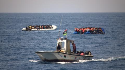 En båt från libyska kustbevakningen åker förbi två gummibåtar packade med migranter och flyktingar.  Bild: Emilio Morenatti/AP/TT