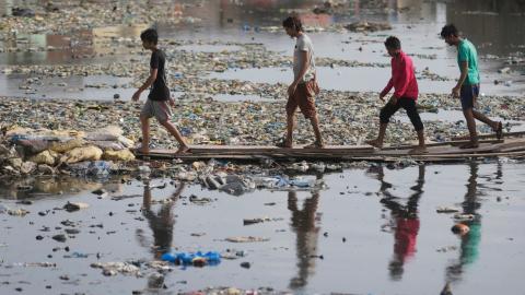En grupp män går genom en vattenkanal förorenad av plast och annat skräp.  Bild: Rafiq Maqbool/AP