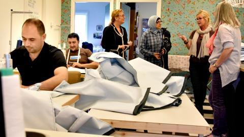 Skräddarna Mohamad Emad Alkasem och  Mahmoud Kaj är igång vid symaskinerna på det sociala företaget Tråd & Trade i Gårdsten. Marie Johansson, handledare, Najah Al-Hamed som hjälper till som tolk, Carina Blomgren och Randi Myhre, båda handledare.