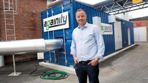David Frykerås framför den nyligen monterade anläggningen hos Norrköping vatten och avfall AB. Överskottsvärme från biogasproduktion genererar el som räcker till 25 hushåll.  Bild: Niclas Sandberg