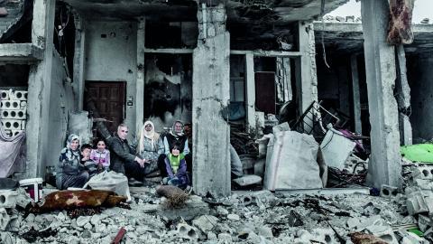 En familj sitter i ruinerna av sitt hus efter IS attack mot Kobane, Syrien.  Bild: Magnus Hjalmarson Neideman/SvD/TT