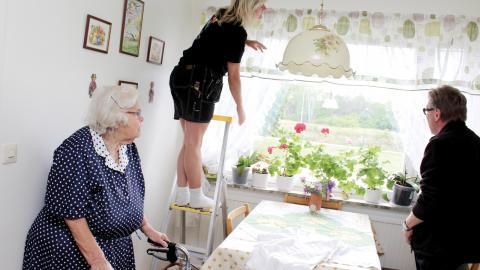 Eva Thos och Michael Ogenbratt från kommunens fixartjänst byter gardiner hemma hos Kerstin Johansson.  Bild: Lisa Karlsson