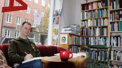 Henrik Johansson sitter i soffan när han läser korrektur eller andra böcker. När han ägnar sig åt skrivandet sitter han i det trånga utrymmet bakom kassan. Bild: Jenny Wickberg