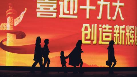 """Människor i Peking passerar  framför en storbildskärm med texten:  """"Välkommen till den 19:e kongressen, skapa ny ära"""" . Kommunistiska partiets kongress inleds i dag i den kinesiska huvustaden. Bild: Ng Han Guan/AP/TT"""
