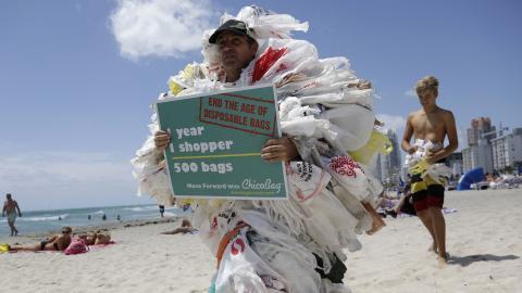 Ett års shopping = 500 plastpåsar. Steve Vincenti protesterar mot plastpåsar på stranden i Miami.  Bild: Lynne SladkyAP/TT