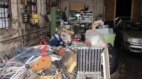 Vid dörrarna vid utgången från byggnaden  förvarades skrot, ved, fordon och livsmedel. Bild: Polisen