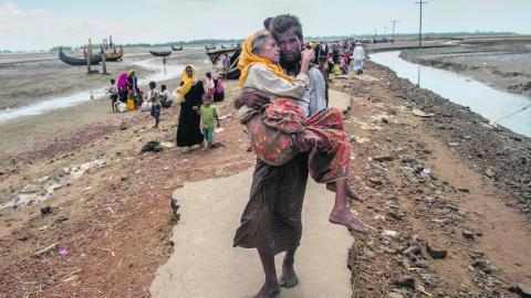 En man bär sin mor på väg till ett flyktingläger för rohingyer i Bangladesh. Det som pågår just nu i Burma är ett regelrätt folkmord. Och det är bråttom attstoppa det, skriver dagens debattörer. Bild: Dar Yasin/ap