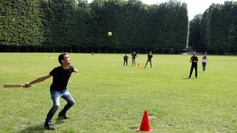 Nittonåriga Kamel Ammauasa slår iväg bollen på brännbollsplanen i den turnering som han själv har varit med och arrangerat.