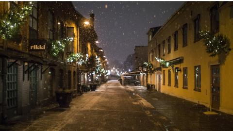 Snön singlar sakta ned över Tändsticksområdets kullerstensgator. Bild: Daniel Johansson
