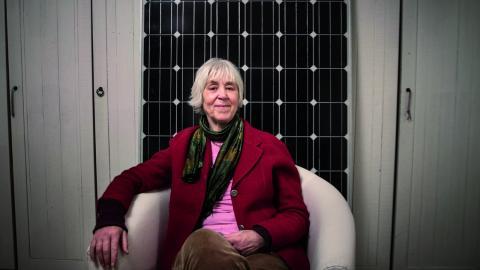 """""""Hittills har mina solceller besparat jorden 2 ton koldioxidutsläpp"""", berättar en nöjd Berenike Alfvén, här framför en solcellspanel. Bild: Hilda Arnebäck"""