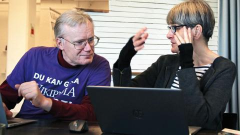 Per Andersson hjälper Anna Selme med några                     tekniska bitar. Gruppen har dock inga utnämnda ledare – både nybörjare och mer inbitna Wikipedianer är lika mycket värda. Foto: Caroline Axelsson