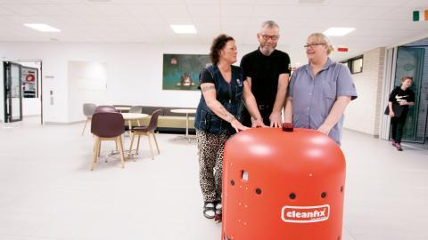 Lokalvårdarna Anette Dahl, Musa Kurti och Jessica Paulsson med städroboten.  Bild: Fredrik Bröndrum/Ängelholms kommun