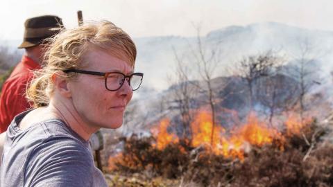 Naturområdesförvaltaren Jeanette Hansson från park- och naturförvaltningen i Göteborg går och släcker efter en av naturvårdsbränningarna på Stora Amundön. Foto: Christopher Kullenberg Rothvall