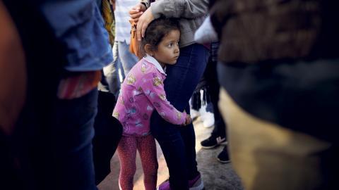 En flicka väntar med sin mamma vid gränsen mellan USA och Mexiko.  TT/AP