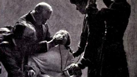 En hungerstrejkande suffragett blir tvångsmatad med hjälp av en slang som sticks ner i näsan.