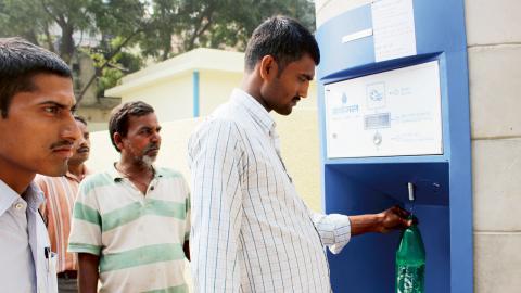"""En man hämtar vatten från en """"vatten-bankomat"""" som drivs med solenergi i slumområdet Savda Ghevra i New Delhi. Bild: Ranjit Devraj/IPS"""