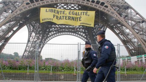 Två poliser går förbi en banderoll som hängts upp på Eiffeltornet av Greenpeace i Frankrike. Bild: Michel Euler/AP/TT