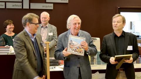 Fjolårets vinnare av Årets Göteborgsbok, Claes Rydholm, tar emot priset av landsarkivarie Ulf Andersson och Robert Berggren, ordförande i Göteborgs hembygdsförbund.  Bild: Riksarkivet Landsarkivet