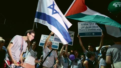 Demonstranter viftar med Israels och Palestinas flagga under en demonstration i Tel Aviv (arkivbild). Bild: Oded Balilty/ap/TT