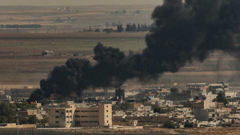 Brinnande byggnader i syriska Ras al-Ayn efter att turkisk militär attackerat staden.  Emrah Gurel/AP