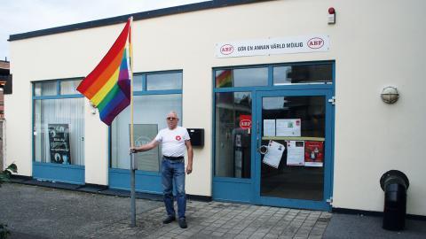 Walter Wege (V) poserar med Pride-flaggan utanför ABF-lokalen i Hörby.   Bild: Gustav Gelin