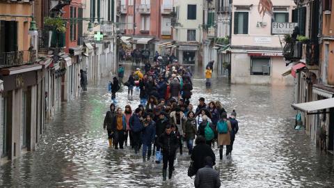 Folk vadar genom vattnet i Venedig på onsdagen. Luca Bruno/AP/TT